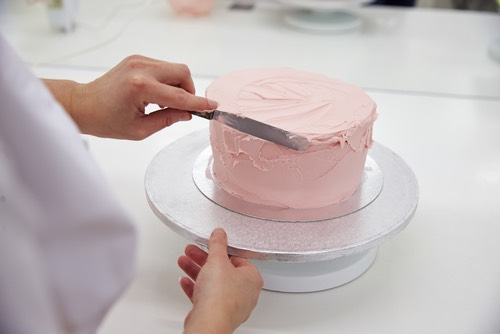 Smoothing the Pink Frosting on a Round Homemade Cake