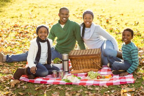 Mother, Father and Two Children Enjoy an Autumn Picnic While Sitting on a Table Cloth