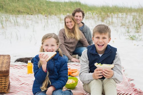 Family of Four Enjoying Picnic Sandwiches on the Beach