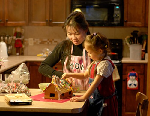 Young Girl Making A Gingerbread House With Mom
