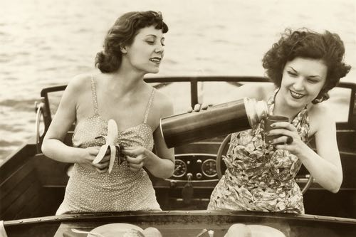 Two Young Ladies Enjoy a Picnic Beverage on a Boat