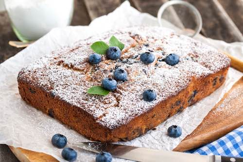 Homemade Blueberry Cake Decorated with Powdered Sugar and Fresh Blueberries