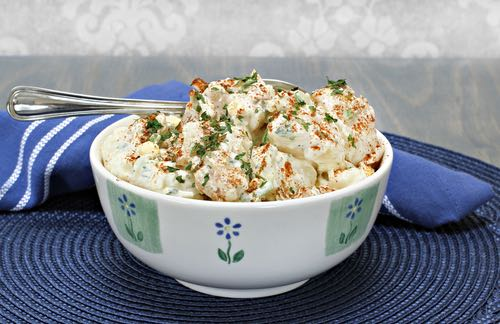Bowl of Homemade Picnic Potato Salad with Eggs, Parsley, and Paprika