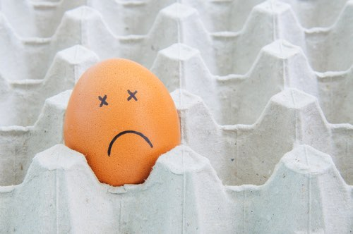 Brown Egg with Sad Face Alone in an Egg Carton