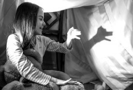 Young Girl Practicing Hand Shadow Puppets