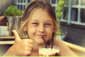 Girl Giving a Thumbs Up to Her Milkshake
