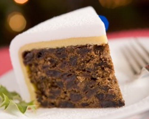 Slice of Christmas Fruitcake with Almond Icing on a Plate