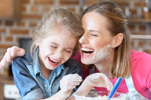 Mother and Daughter Laughing While Baking