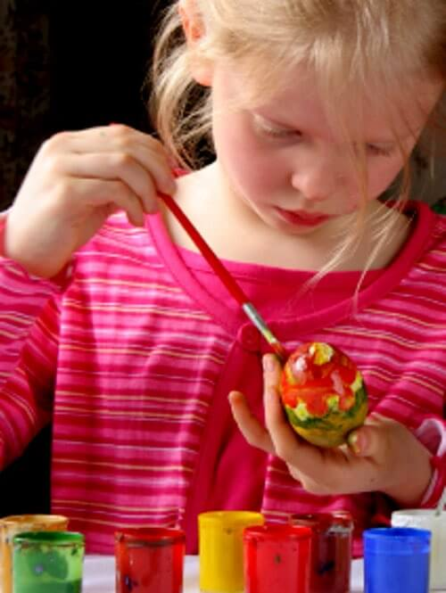 Girl Having Fun Coloring Easter Eggs