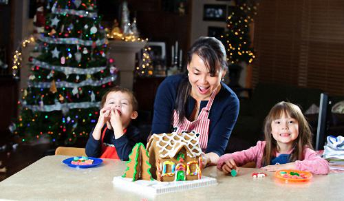 Mom Showing Kids How to Make a Gingerbread House