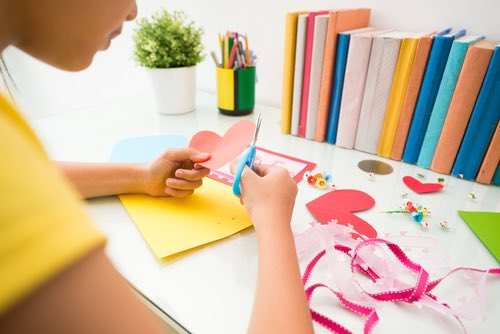 Young Girl Cutting Out a Card for Valentine Day