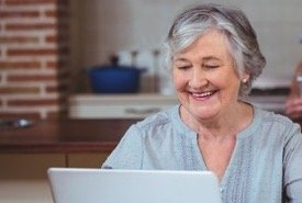 Lady Reading Kitchen Hints for Cooking on Her Laptop