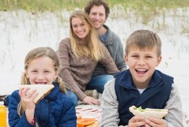 Family Eating Picnic Sandwiches on the Beach