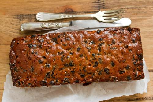 Traditional English Fruitcake with Knife and Fork on a Table