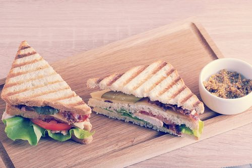 Vintage Toasted Club Sandwich Served with White Mustard on a Rectangular Wooden Plate